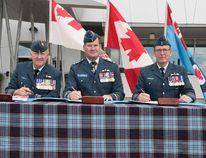8 Wing Imaging/Cpl. Rod Doucet Incoming commanding officer Colonel Shayne Elder, presiding officer of the ceremony, Lieutenant-General Mike Hood, and outgoing commanding officer Colonel Kelvin Truss sign papers during the change of command ceremony for Canadian Force Aerospace Warfare Center at CFB Trenton.