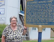 Cobalt Mayor Tina Sartoretto stands in front of the memorial to Willet Green Miller, the Ontario geologist who gave the town its name. Sartoretto is cautiously optimistic about drilling activity taking place in the region for the mineral cobalt, used in the manufacture of lithium-ion batteries. PJ Wilson/The Nugget