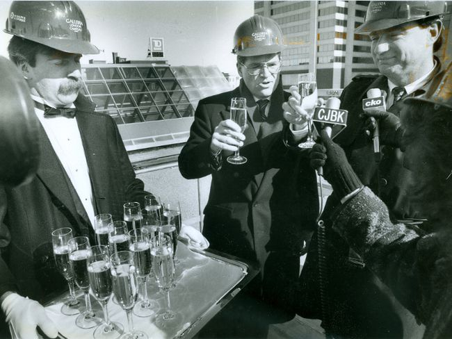 Vice-president Paul Campbell, centre and London Mayor Tom Gosnell are served champagne by Mark Gorden during a ceremony to mark the completion of work on Galleria London's exterior, 1989. (London Free Press files)