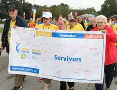 BRUCE BELL/the intelligencer Dr. Douglas MacIntosh (left) his wife Catherine (far right) get a hand from cancer survivors Donna Nixon (second from left) and Candace O'Hara with the Relay for Life banner during the Survivor Lap Friday night at Loyalist College.
