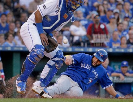 Blue Jays' Kendrys Morales beats the tag by Royals catcher Salvador Perez to score during their game in Kansas City last night. Morales got a warm reception from his former team. (AP)