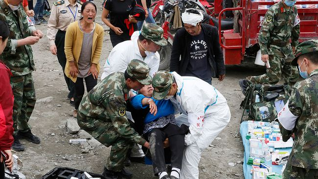 An elderly woman faints upon seeing the bodies of her dead relatives at the site of a landslide in Xinmo village in Maoxian County in southwestern China's Sichuan Province, Sunday, June 25, 2017.  (AP Photo/Ng Han Guan)