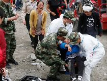 An elderly woman faints upon seeing the bodies of her dead relatives