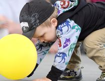 """Maverick Sharpe, 2, keeps busy with a yellow balloon during the 12th annual Kidz Safety Summer Festival on Sunday at Roberta Bondar Pavilion. Sharpe enjoyed visiting Sault Ste. Marie Fire Services, meeting Canadian Bushplane Hertiage Centre's beaver mascot, a free juice box and a ride with Algoma Model Engineering Society. """"He had fun,"""" said Sharpe's father, Ryan. More than two dozen agencies, including Canadian Red Cross, Sault Search and Rescue, John Rhodes Community Centre and Electrical Safety Authority offered tips to keep kids safe during the school break."""