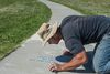 Vlad Varbanov was sandblasting poetry into the sidewalks  bordering Mill Creek as part of the a community art project  in the Meadows on June 25, 2017. The poetry was submitted by school children and residents of the area.  Photo by Shaughn Butts / Postmedia