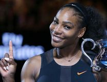 In this Jan. 28, 2017, file photo, Serena Williams holds up a finger and her trophy after defeating her sister, Venus, in the women's singles final at the Australian Open tennis championships in Melbourne, Australia. Williams posed nude for the cover of Vanity Fair in an image released by the magazine on June 27, 2017. (AP Photo/Aaron Favila, File)