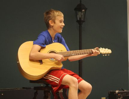Aidan Benton, from Avon Public School, plays The Hockey Song on guitar at a celebration to wrap up a yearlong learning partnership between Grade 6 students and local seniors with dementia. (MEGAN STACEY/The Beacon Herald)
