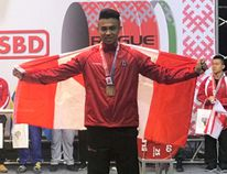 Christopher Dang stands on the podium after earning a bronze medal in the deadlift at the International Powerlifting Federation championships in Belarus. (Contributed photo)