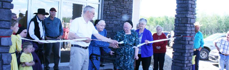 Clear Hills County councillor held the ribbon steady while Mrs. Carter, Mrs. Braun and Mrs. Fletcher cut the ribbon to declare the second phase of the Cleardale Seniors Residence officially open June 24.