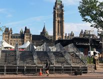 Temporary stairs are installed over the fence in front of Parliament Hill, in preparation of the upcoming Canada Day celebrations, in Ottawa on Wednesday, June 28, 2017. (Fred Chartrand/The Canadian Press)