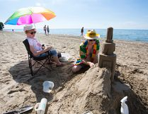 Gary Burnett builds a sand castle while wife Corinne Burnett relaxes during a warm afternoon at Lakeside Park Beach at St. Catharines, in this file photo from June 2015. (File photo/Postmedia Network)