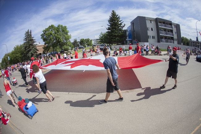 A giant Canadian flag, held by several volunteers, is carried during the annual Canada Day parade along Franklin Avenue in downtown Fort McMurray Alta. on Saturday July 1, 2017. Robert Murray/Fort McMurray Today/Postmedia Network