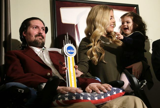 FILE - In this Dec. 13, 2016, file photo, former Boston College baseball captain Pete Frates, left, appears with his wife Julie, center, and two-year-old daughter Lucy, right, moments after he was presented with the 2017 NCAA Inspiration Award, at their home in Beverly, Mass.(AP Photo/Steven Senne, File)