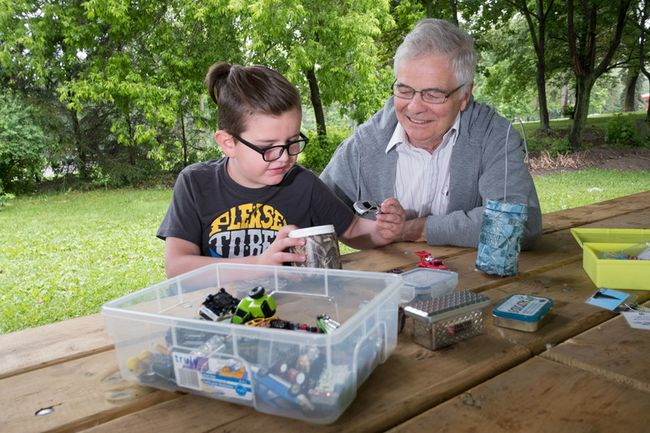 Dakota Williams, 7, having found a cache, prepares to make a trade from her geocaching Grampa Doug Offord's collection.