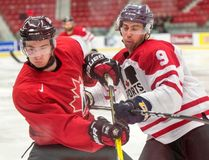 Queen's defenceman Spencer Abraham, right, of the Canadian University All-Stars checks Nicolas Roy of the Team Canada juniors during exhibition hockey action on Dec. 13 in Boisbriand, Que. (Ryan Remiorz/The Canadian Press)