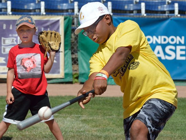 Andre Thompson, 11, pounds out a hit in front of catcher Todd Joseph, 5, on training day Wednesday for the 24th annual Rookie League at Labatt Park. (MORRIS LAMONT, The London Free Press)