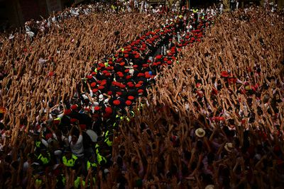 A municipal musical band prepare while revellers hold up neckties during the launching of the 'Chupinazo' rocket, to celebrate the official opening of the 2017 San Fermin Fiestas in Pamplona, Spain, Thursday July 6, 2017. The first of eight days of the running of the bulls along the streets of the old quarter of Pamplona starts Friday. (AP Photo/Alvaro Barrientos)