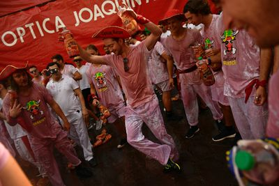 A reveller dances after the launching of the 'Chupinazo' rocket, to celebrate the official opening of the 2017 San Fermin Fiestas in Pamplona, Spain, Thursday July 6, 2017. The first of eight days of the running of the bulls along the streets of the old quarter of Pamplona starts Friday. (AP Photo/Alvaro Barrientos)