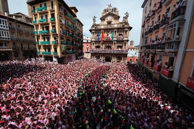 """The """"Pamplonesa"""" municipal music band performs during the launch of the 'Chupinazo' (start rocket) to mark the kickoff at noon sharp of the San Fermin Festival, in front of the Town Hall of Pamplona, northern Spain, on July 6, 2017. A red-and-white sea of revellers soaked each other with wine in a packed Pamplona square today to kick off Spain's most famous fiesta, the San Fermin bull-running festival. (ANDER GILLENEA/AFP/Getty Images)"""