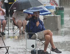Johnny Mills attempts to brave the rain during Friday night's Sunfest downpour at Victoria Park. (CHARLIE PINKERTON/London Free Press/Postmedia Network)