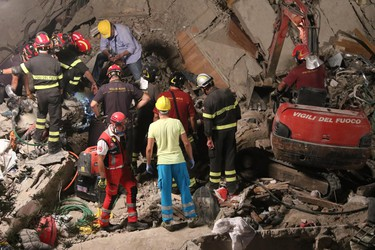 Rescuers work amid the rubble of a building that collapsed in Torre Annunziata, near Naples, southern Italy, Friday, July 7, 2017. (Italian Firefighters via AP)