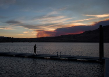 A woman walks on a dock at Kamloops Lake in Savona, B.C., as smoke from a wildfire burning near Ashcroft rises in the distance at sunset on Friday July 7, 2017. THE CANADIAN PRESS/Darryl Dyck