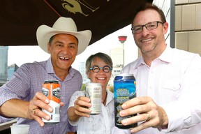 L-R, Joe Ceci, President of Treasury Board and Minister of Finance toasts with Calgary Councillor, Druh Farrell and Terry Rock, Executive Director of the Alberta Small Brewers Association after announcing a new policy to make it easier for licensed venues in Alberta to have greater control over the size of their patios and fewer restrictions on how they are built at the King Eddy in Calgary on Sunday July 9, 2017. DARREN MAKOWICHUK/Postmedia Network