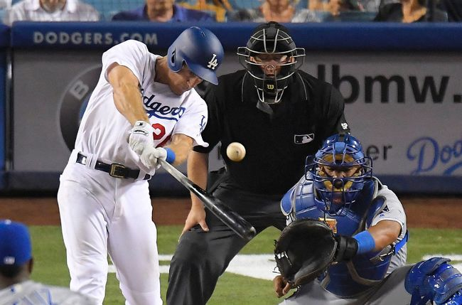 Los Angeles Dodgers' Chase Utley hits an RBI double as Kansas City Royals catcher Salvador Perez, right, and home plate umpire Todd Tichenor watch Friday, July 7, 2017, in Los Angeles. (AP Photo/Mark J. Terrill)