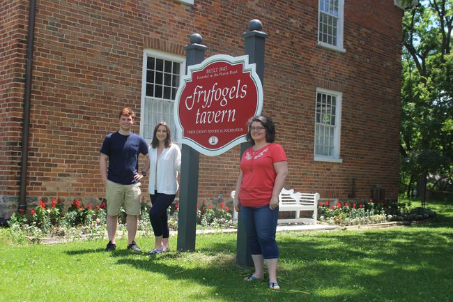 Summer students Jake Dickey and Justina Reinhart (left) join board director Kathryn Haynes (right) at Fryfogels Tavern, a historical landmark just outside Shakespeare. Dickey and Reinhart will ensure the old tavern can stay open for visitors Wednesday through Sunday in the summer months. (MEGAN STACEY/The Beacon Herald)