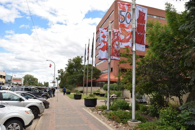 Banners celebrating Canada's 150th birthday flutter in the breeze in front of city hall in Fort McMurray, Alta. on Friday, July 7, 2017. Cullen Bird/Fort McMurray Today/Postmedia Network