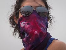 Luana Avila wears a bandana over her face because of smoke and ash in the air from wildfires