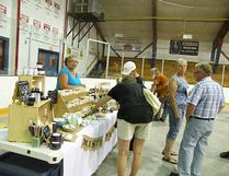 Ron Rauckman (far right) stops to have a look at the handcrafted natural soap offered by Misty Meadows at the Heart of the Peace Public Market in the Fairview Arena July 8.