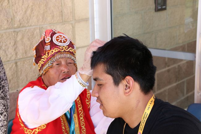 A Siberian Elder gives a youth a traditional therapy.