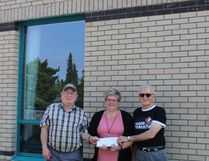 Lance Walton hands a cheque for Bud Jardine's wedding performance to Kids First Executive Director Jan Boughen.