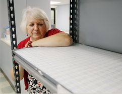 Luke Hendry/The Intelligencer Operations director Susanne Quinlan stands next to empty shelves at Gleaners Food Bank in Belleville Wednesday. There is much food in the warehouse, she said, but donations of staple foods are needed.
