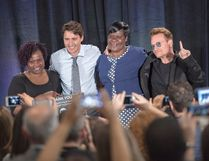 Prime Minister Justin Trudeau, rock band U2's Bono, right, and AIDS activists Patricia Aserrio Ochieng and Consolata Opiyo, left, pose for photos after a town hall meeting for the One Campaign for the fight against poverty, in Montreal on Saturday, September 17, 2016. THE CANADIAN PRESS/Ryan Remiorz