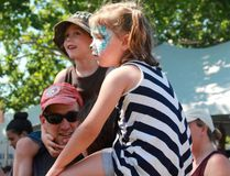 Charlie (6) and Gemma (5) Gould hang out with their parents, Ryan Gould and Nikki Favalaro near the children's stage at Home County Music and Art Festival on Saturday, Jul. 15 (Shalu Mehta/The London Free Press).