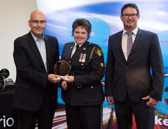 The Honourable Steven Del Duca, left, Ministry of Transportation, presents Const. Beth Ethier (retired) with the 2017 Road Safety Achievement Award in the Professional Category. They stand with nominator Brian Brohart, health promoter from the Renfrew County and District Health Unit and chairman of the Renfrew County Police Committee.