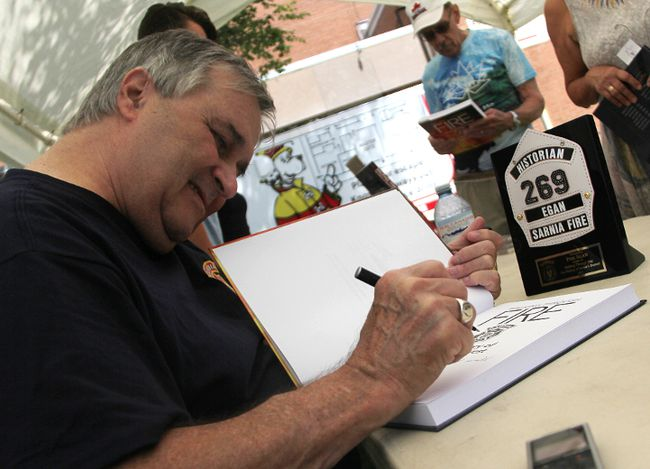Phil Egan signs a copy of his book Walking Through Fire, a history of Sarnia's fire service, at an event Saturday in Sarnia. The historian was honoured by firefighters for his work. Tyler Kula/Sarnia Observer/Postmedia Netwo