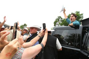 Prime Minister Justin Trudeau waves goodbye with a cowboy salute during a stop at Parkdale Community Association for a pancake breakfast in Calgary, AB on Saturday July 15, 2017. Jim Wells/Postmedia Network