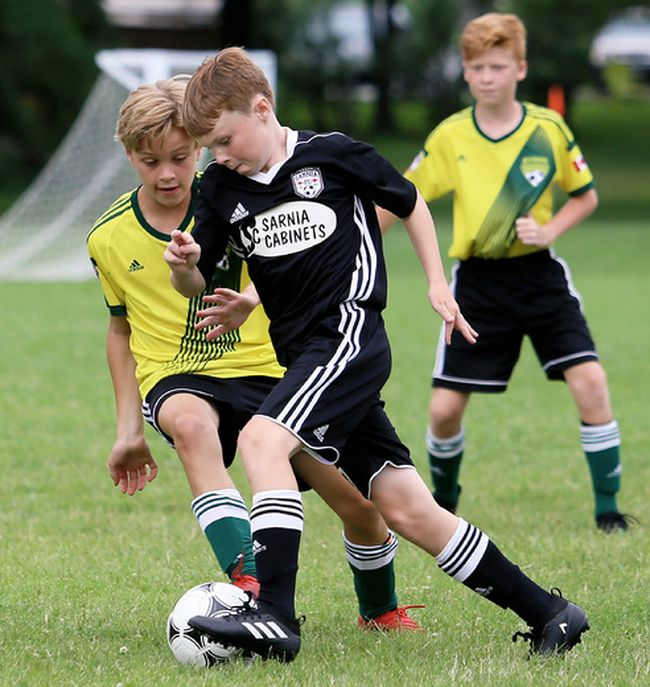 Liam Burwell of Sarnia FC protects the ball from Byron's Jack Builder during an under-12 boys' game in the seventh annual Water's Edge Classic at Germain Park on Sunday, July 16, 2017. The Sarnia FC-hosted tournament had a record 95 boys' and girls' teams, the most ever for a Sarnia soccer tournament. The teams filled every hotel room in the city, said tournament director Dean Troiani. (MARK MALONE/Postmedia Network)