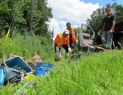 Officials at Aamjiwnaang First Nation are raising alarm over illegal dumping they say happens regularly on the community's roads. From left, public works staff Kevin Maness and Bob Rogers, and public works co-ordinator Brian Bois, deal with garbage found along a section of Williams Drive Friday July 14, 2017. (Paul Morden/Sarnia Observer/Postmedia Network)