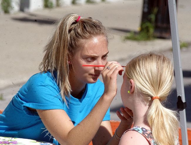 Emily Sellner paints a youngster face, as large crowds came down to Wallyfest on Saturday, to check out a variety of vendors, family entertainment and farmer's market.