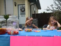 Kaylee Simard (left) and Ellie-Anna Fuoco sell lemonade, candy and popsicles for charity at their stand on 55 Ave. on June 10 (Peter Shokeir   Whitecourt Star).