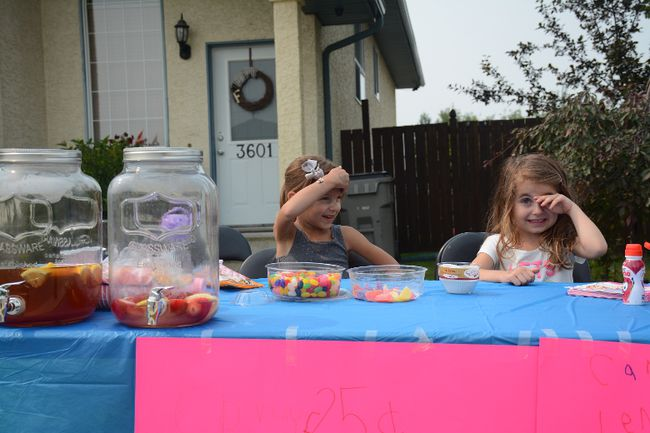 Kaylee Simard (left) and Ellie-Anna Fuoco sell lemonade, candy and popsicles for charity at their stand on 55 Ave. on June 10 (Peter Shokeir | Whitecourt Star).