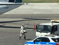 A beekeeper works to clear a large swarm of bees away from an airport vehicle at the Saskatoon Airport on Sunday July 16, 2017. (Submitted photo)