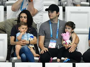 Mila Kunis, left, and her husband US actor Ashton Kutcher, center, are seen with their children during the women's 3m synchro springboard final of the 17th FINA Swimming World Championships in Duna Arena in Budapest, Hungary, Monday, July 17, 2017. (Tibor Illyes/MTI via AP)