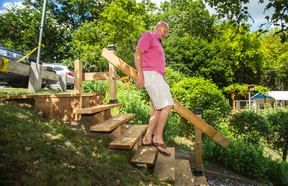 Adi Astl poses for a photo at the top of the staircase he built leading down to Tom Riley Park, near Islington Ave. and Bloor St. W., in Toronto on Tuesday July 18, 2017. (Ernest Doroszuk/Toronto Sun)