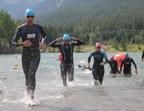 Athletes leap from the water to complete another lap during the 2017 Canmore Open Water Swim held at Quarry Lake Park in Canmore on Saturday, July 15, 2017. (Patrick Gibson/ Bow Valley Crag & Canyon)