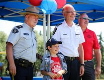 Kolby Szerve, seen here between S/Sgt. Ken Morrison and LPS Chief Lorne Blumhagen, dressed the part of a police officer himself for his graduation from Big Brothers Big Sisters' Kids 'n Kops program on Friday afternoon at MEGlobal Athletic Park. (Ashli Barrett/Lacombe Globe)